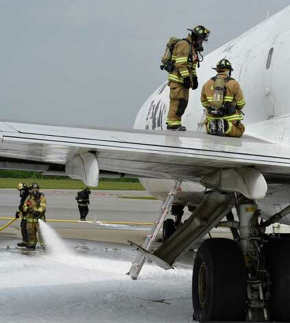Firefighters perform a rescue scenario through the emergency doors on the side of the fuselage of a former FedEx Boeing 727 Friday morning, June 12, 2015, which is now a full-time member of the airport fire department after it's donation at Albany International Airport  in Colonie, N.Y.  It will be used for fire training evolutions.  (Skip Dickstein/Times Union) Photo: SKIP DICKSTEIN / 00032263A