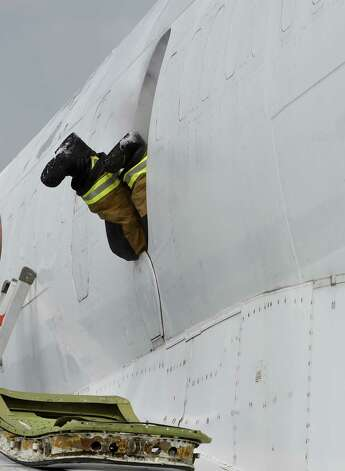 Firefighters perform a rescue scenario through the emergency doors on the side of the fuselage of a former FedEx Boeing 727 Friday morning, June 12, 2015, which is now a full-time member of the airport fire department after its donation at Albany International Airport  in Colonie, N.Y.  It will be used for fire training evolutions.  (Skip Dickstein/Times Union) Photo: SKIP DICKSTEIN / 00032263A