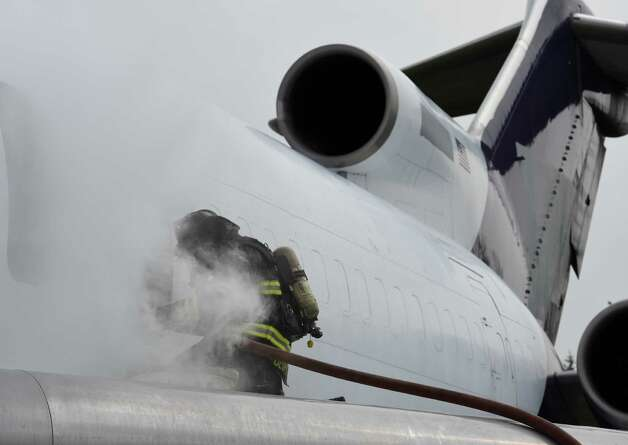 Firefighters perform a rescue scenario through the emergency doors on the side of the fuselage of a former FedEx Boeing 727 Friday morning, June 12, 2015, which is now a full time member of the airport fire department after its donation at Albany International Airport  in Colonie, N.Y.  It will be used for fire training evolutions.  (Skip Dickstein/Times Union) Photo: SKIP DICKSTEIN / 00032263A