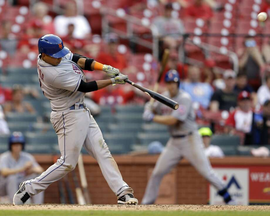 New York Mets' Ruben Tejada hits a sacrifice fly to score teammate Wilmer Flores during the 18th inning of a baseball game Sunday, July 19, 2015, in St. Louis. (AP Photo/Jeff Roberson) Photo: Jeff Roberson, Associated Press