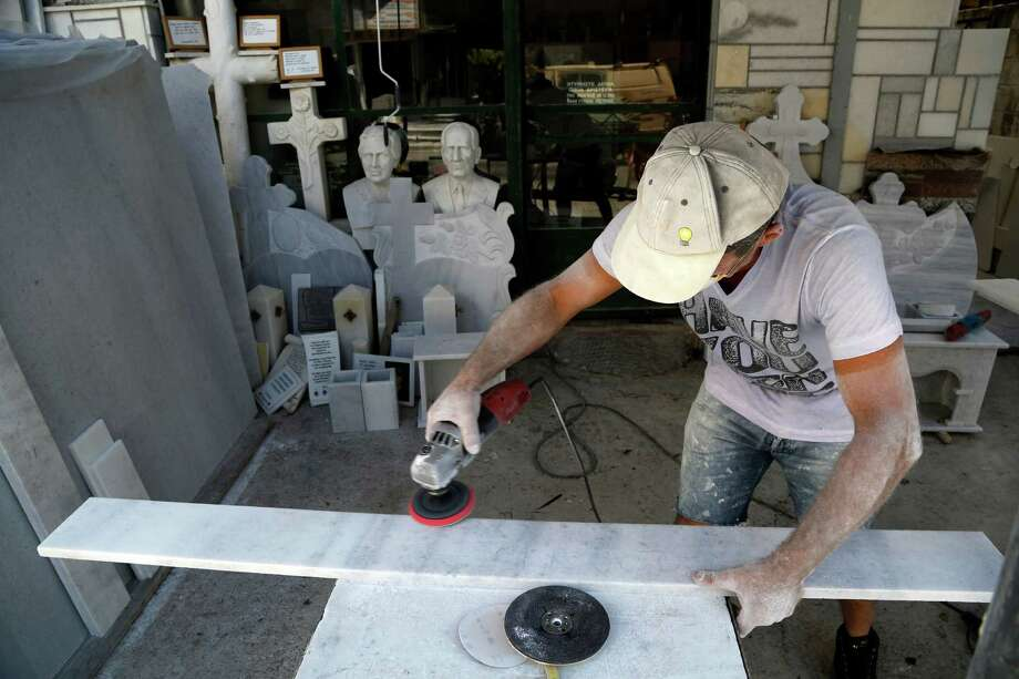 A mason works on a marble headstone in Athens. With most funerals in Greece paid for in cash in advance, funeral homes are struggling to cope with cash withdrawal restrictions. Photo: Petros Karadjias, STF / AP