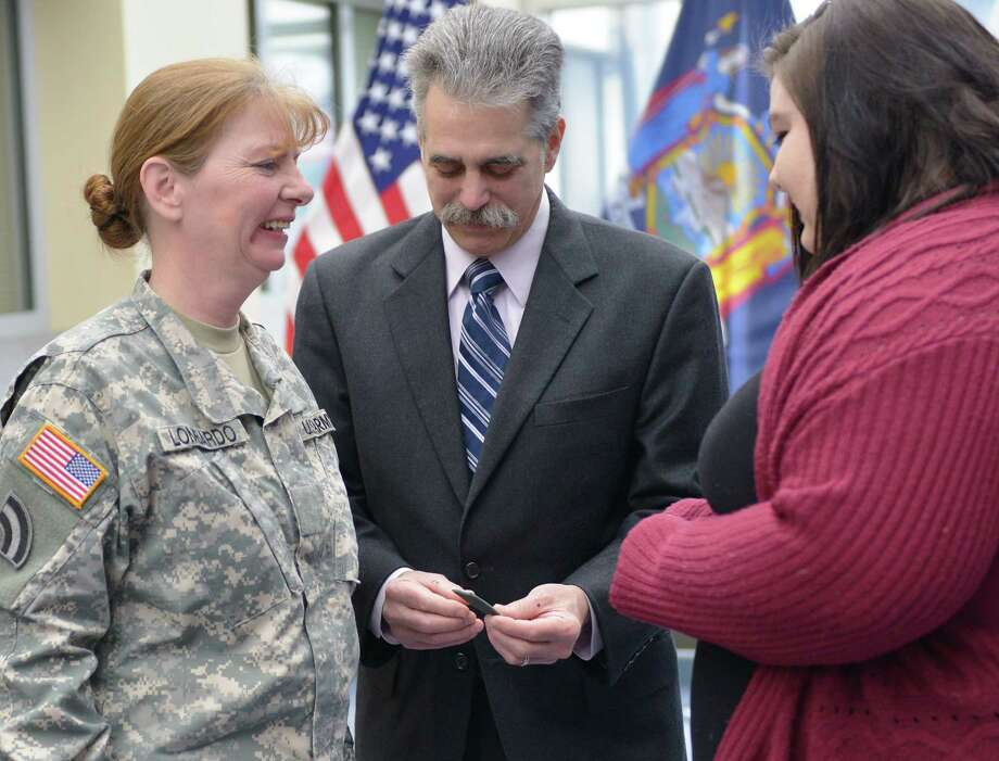 New York Army National Guard Corine Lombardo receives her new sergeant major rankfrom her husband Randy and daughter Sabrina during a promotion ceremony.