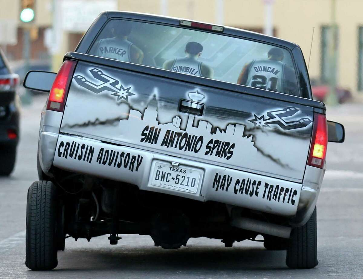 A Spurs fan drives through Alamo Plaza during a march and rally to the Alamo to welcome new players LaMarcus Aldridge, David West, and others to the team Sunday July 19, 2015.