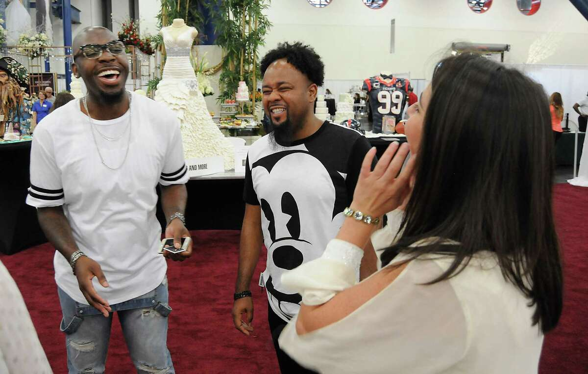 Quinn Newsome, left, and his partner Rashaan Nowell talk wedding plans Sunday with Melissa Birch from Tomball's Moffitt Oaks at the Houston Bridal Extravaganza.