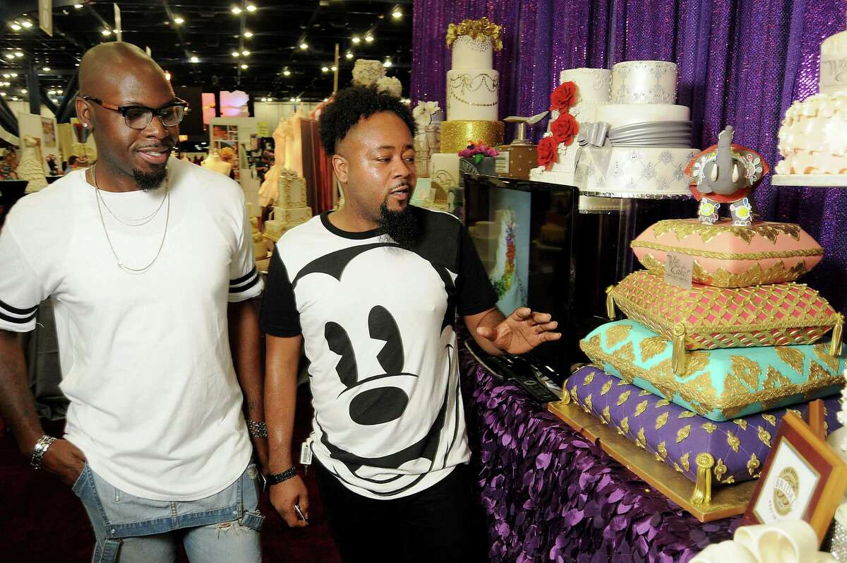 """Engaged couple Quinn Newsome and Rashaan Nowell browse the wedding cakes on Sunday in the """"Who Made the Cake?"""" booth at the Houston Bridal Extravaganza at the George R. Brown Convention Center."""