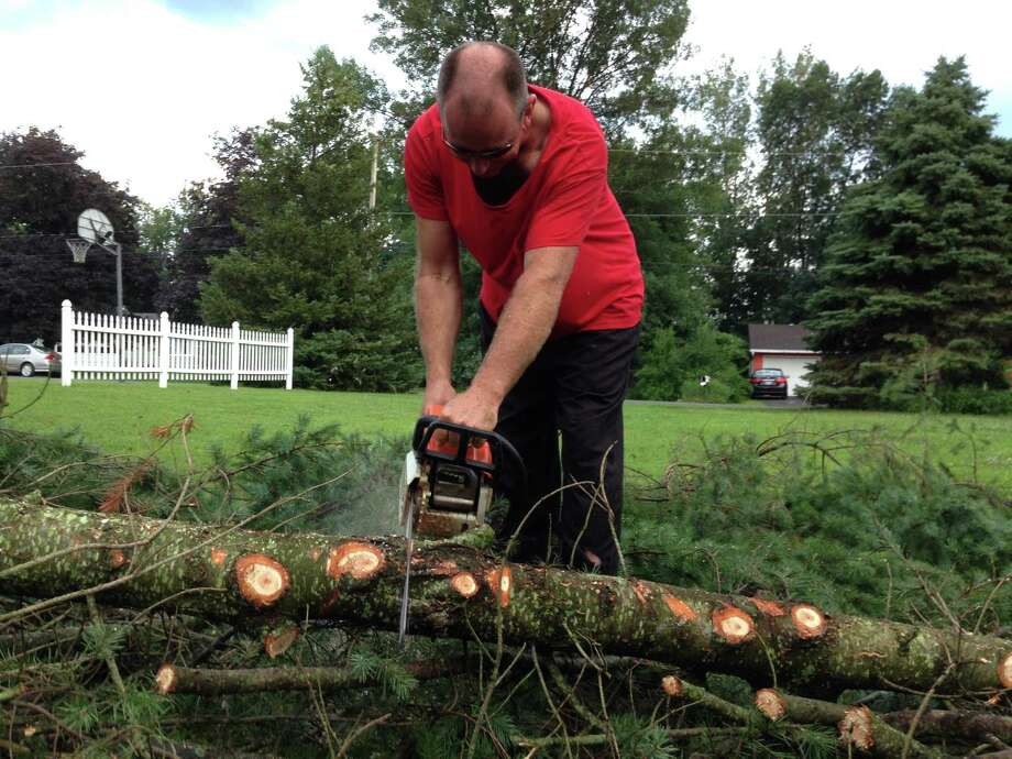 Troy DenBesten cuts up a tree that fell into a neighbors yard during severe weather that blew through Valatie, N.Y., Sunday, July 19, 2015.