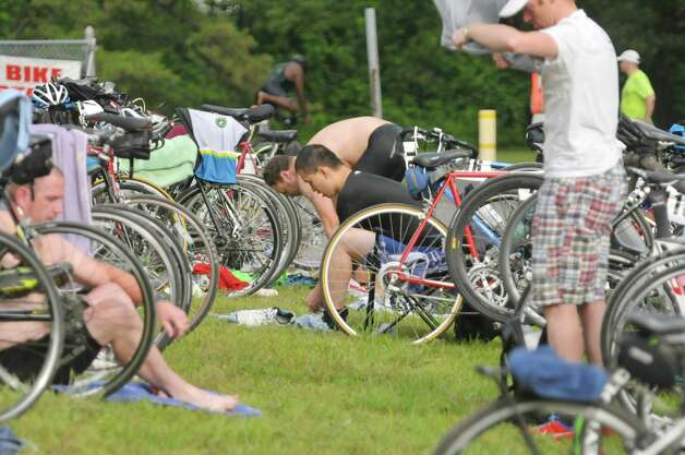 Competitors switch their gear for the bicycle ride portion of the Pine Bush Triathlon at Rensselaer Lake on Sunday, July 19, 2015, in Albany, N.Y.  The contest consists of a 325 yard swim, a 11.5 mile bike ride and a 3.25 mile run, ending at the Guilderland YMCA.   (Paul Buckowski / Times Union) Photo: PAUL BUCKOWSKI / 00032634A