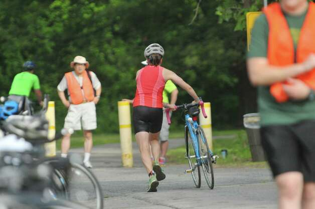A competitor runs with her bike to the start of the bicycle riding portion of the Pine Bush Triathlon at Rensselaer Lake on Sunday, July 19, 2015, in Albany, N.Y.  The contest consists of a 325 yard swim, a 11.5 mile bike ride and a 3.25 mile run, ending at the Guilderland YMCA.   (Paul Buckowski / Times Union) Photo: PAUL BUCKOWSKI / 00032634A