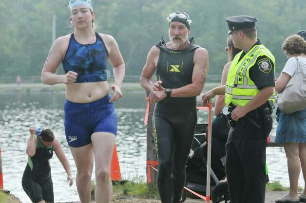 Competitors come out of the water and make their way to their bicycles in the Pine Bush Triathlon at Rensselaer Lake on Sunday, July 19, 2015, in Albany, N.Y.  The contest consists of a 325 yard swim, a 11.5 mile bike ride and a 3.25 mile run, ending at the Guilderland YMCA.   (Paul Buckowski / Times Union) Photo: PAUL BUCKOWSKI / 00032634A