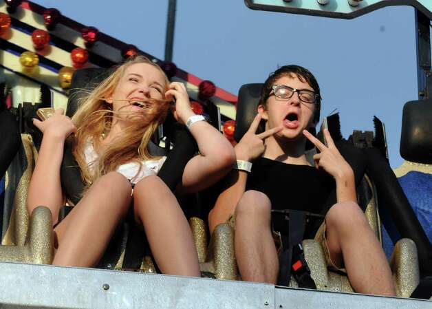 Kaylyn Zyzkowski, left, of New Jersey and Jonathan Witfield of New York City enjoy a ride on the Avalanche ride during the Altamont Fair on Tuesday, Aug. 13, 2013, in Altamont, N.Y. (Michael P. Farrell/Times Union) Photo: Michael P. Farrell / 00023489A