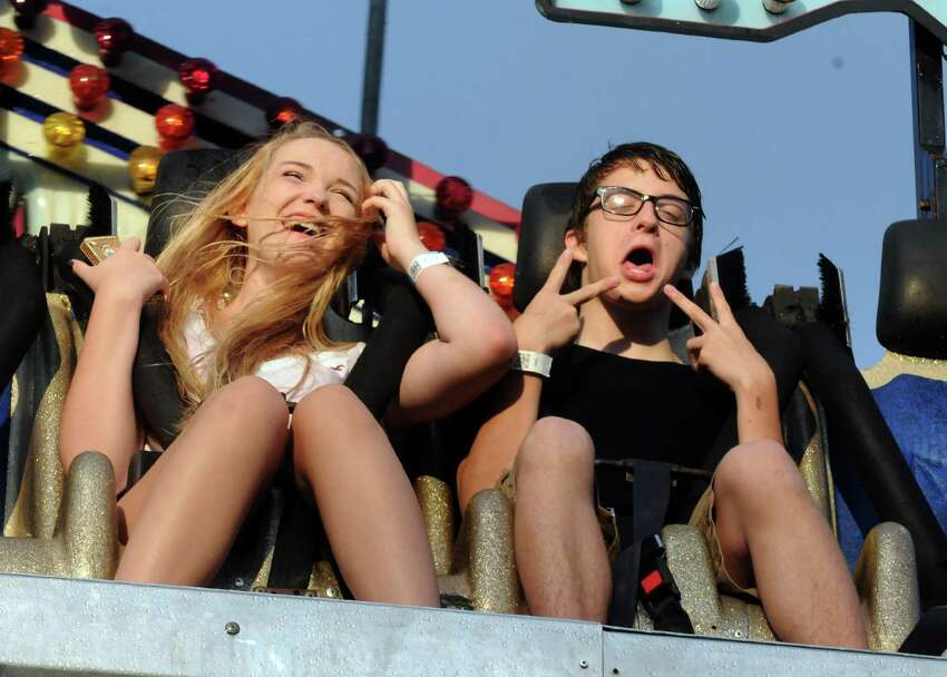 Kaylyn Zyzkowski, left, of New Jersey and Jonathan Witfield of New York City enjoy a ride on the Avalanche ride during the Altamont Fair on Tuesday, Aug. 13, 2013, in Altamont, N.Y. (Michael P. Farrell/Times Union)