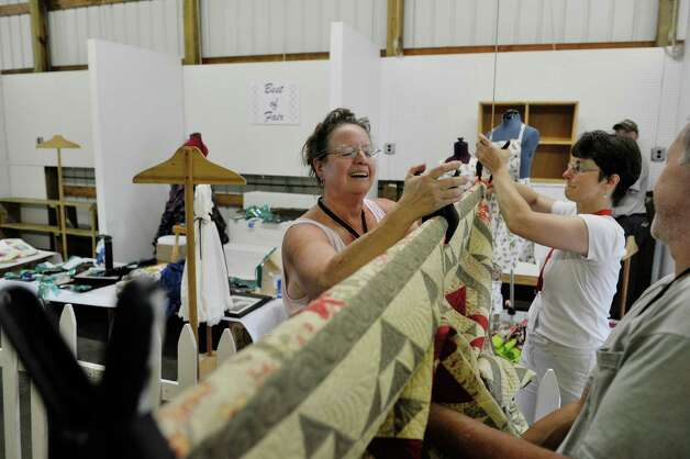 Volunteers, Lanie Kosower, left, and Ellen Tucker-Cohen hang one of the hand-made quilts inside the Home Arts/Fine Arts building as set up continues for the Saratoga County Fair on Sunday, July 19, 2015, in Ballston Spa, N.Y.  Kosower and Tucker-Cohen have volunteered for the past four years.  The fair opens on Tuesday.     (Paul Buckowski / Times Union) Photo: PAUL BUCKOWSKI / 00032673A