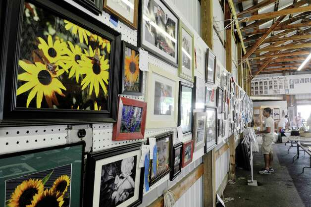 Volunteers hang the photography contest images inside the Home Arts/Fine Arts building as set up continues for the Saratoga County Fair on Sunday, July 19, 2015, in Ballston Spa, N.Y.  The fair opens on Tuesday.     (Paul Buckowski / Times Union) Photo: PAUL BUCKOWSKI / 00032673A