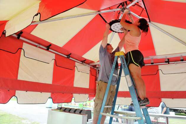 Willam Scannell and his wife Priscilla Scannell from Cape Coral, FL, hang a light as they set up their food concession stand, Butcher Boys, as they get ready for the Saratoga County Fair on Sunday, July 19, 2015, in Ballston Spa, N.Y.   The fair opens on Tuesday.     (Paul Buckowski / Times Union) Photo: PAUL BUCKOWSKI / 00032673A