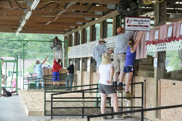Families start to hang up items in the cow barn as set up continues for the Saratoga County Fair on Sunday, July 19, 2015, in Ballston Spa, N.Y.  The fair opens on Tuesday.     (Paul Buckowski / Times Union) Photo: PAUL BUCKOWSKI / 00032673A