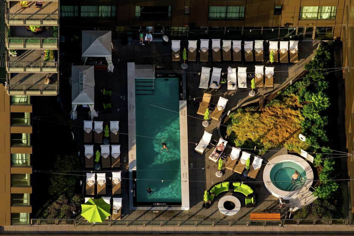 An aerial view is shown of swimmers and loungers enjoying a summer evening downtown on one of Seattle's many roof decks. Photographed on Wednesday, July 15, 2015, from a helicopter.