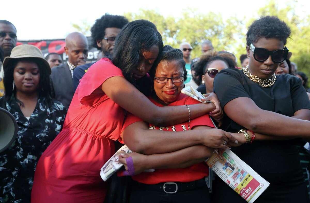 Lanitra Dean hugs Carlesha Harrison, a friend of Sandra Bland, during a vigil Sunday in Prairie View.
