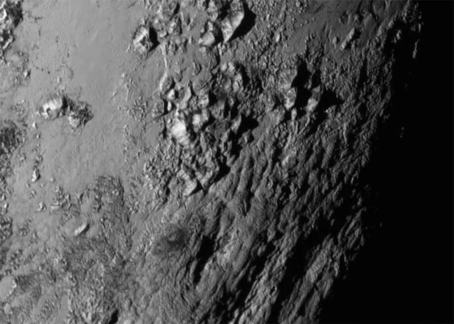 Stand-alone photo of Pluto, released Wednesday: Mountains as high as 11,000 feet above the equator of the dwarf planet. Photos have also shown that the surface of Pluto seems to be much smoother than that of Charon. Illustrates PLUTO (category a) (c) 2015, The Washington Post. Moved Thursday, July 16, 2015. (MUST CREDIT: NASA/Johns Hopkins University Applied Physics Laboratory/Southwest Research Institute.) Photo: POST, STR / THE WASHINGTON POST