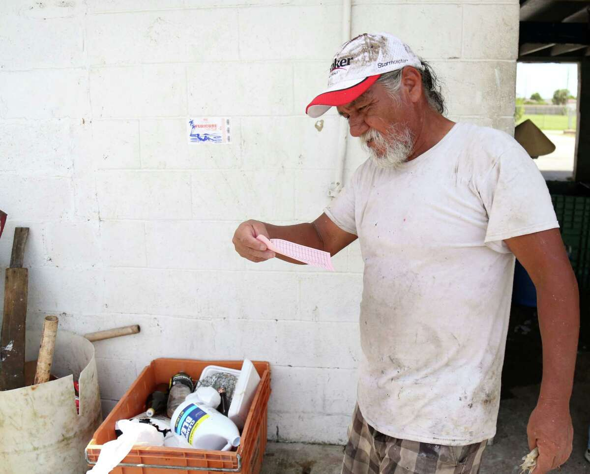 Frank Gonzales, a fisherman of 27 years, checks the ticket he received for delivering 200 lbs. of fresh shrimp at C & H Seafood Friday, July 17, 2015, in San Leon. Many fishermen spoke of selling shrimp for $.35-$.40 per pound.