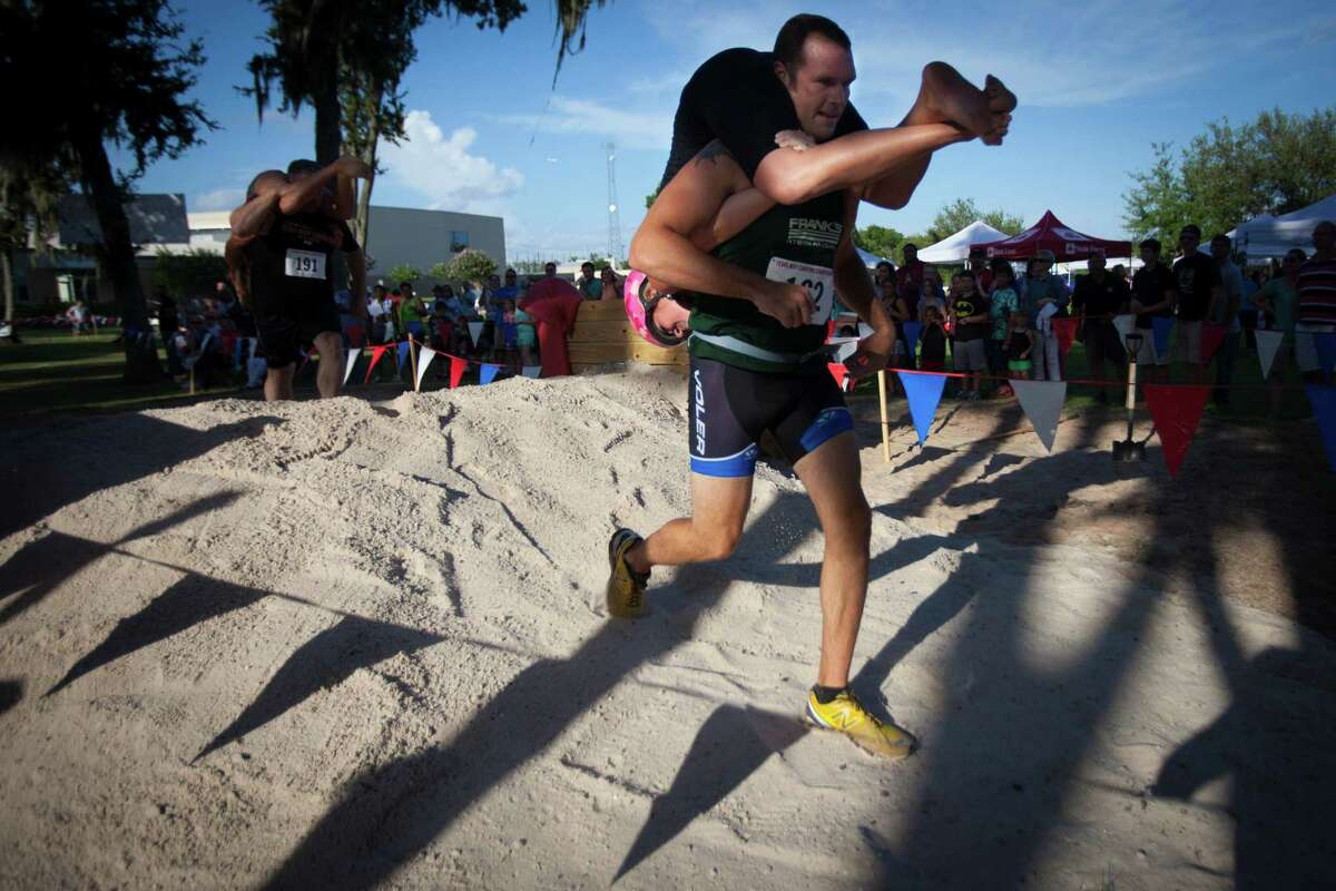 Drew Ludlow carries his wife Jennifer Ludlow during the 2015 Texas Wife Carrying Championship, Saturday, July 18, 2015, in Houston.