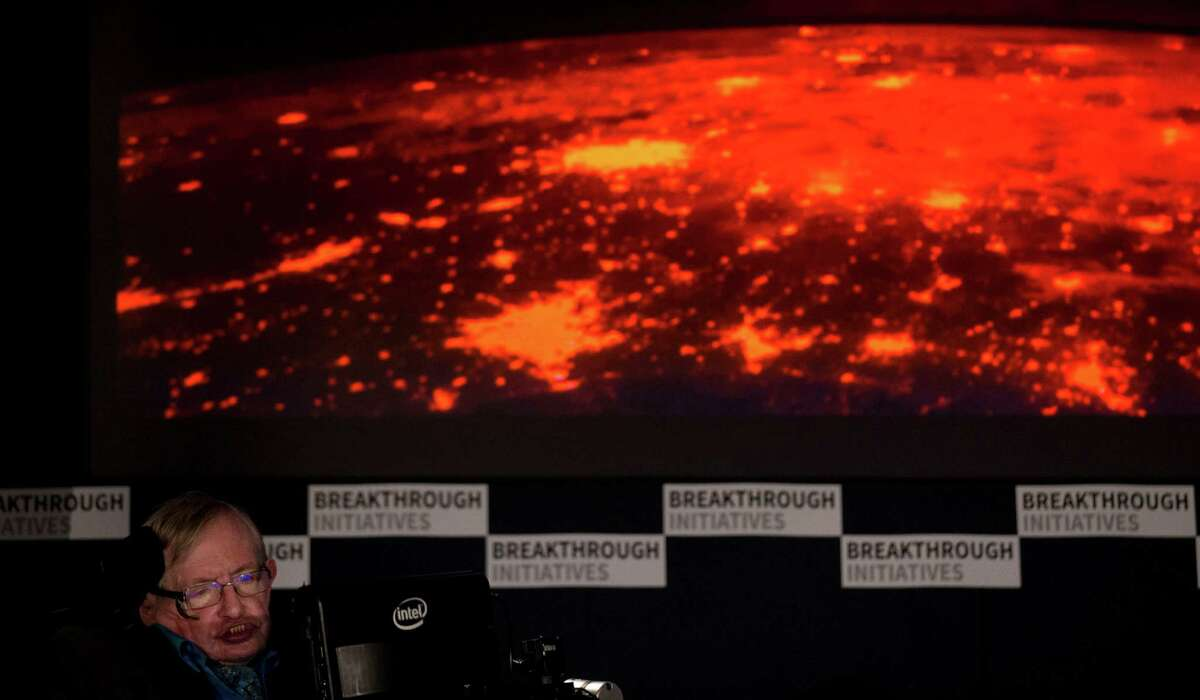 Renowned physicist Stephen Hawking sits in front of a presentation image during a press conference in London, Monday, July 20, 2015. Hawking and Russian tech entrepreneur Yuri Milner are pushing the search for extraterrestrial life into higher gear. The pair said Monday the $100 million