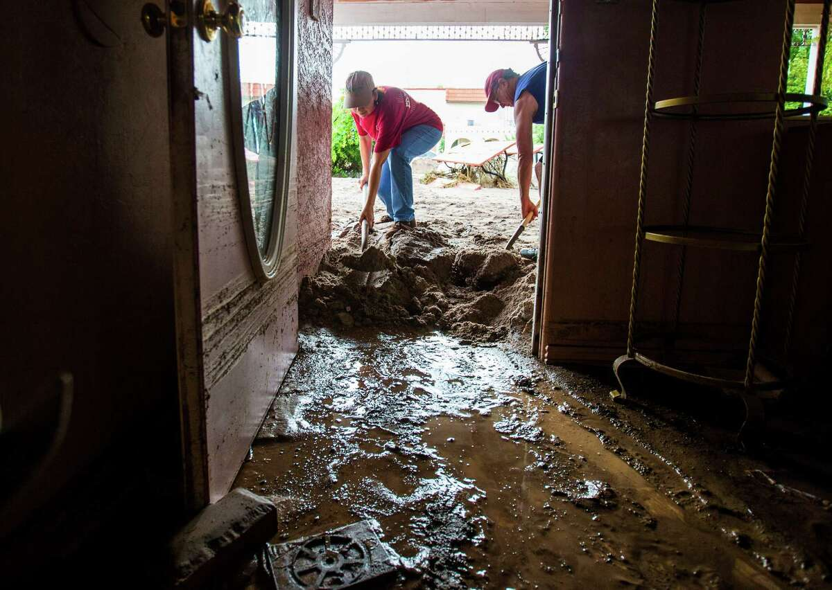 Tammy Heath, left, and Vern Crissman help a resident dig out mud from her house for the second time in less than a year, in Wickenburg, Ariz., Sunday July 19, 2015. The National Weather Service says between 1 and 4 inches of rain fell in and around Wickenburg Saturday afternoon in a 90-minute period. (Michael Chow/The Arizona Republic via AP) MARICOPA COUNTY OUT; MAGS OUT; NO SALES; MANDATORY CREDIT