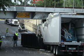 Crews clean up spilled milk and other debris Monday July 20, 2015 after a tractor trailer rig hit the underside of a railroad bridge on South St. Mary's Street about 5:30 a.m. near Brackenridge High School. Police at the scene said the driver was not injured and all of the food products on the truck were considered contaminated and would be disposed of. The street has been closed off for more than three hours.