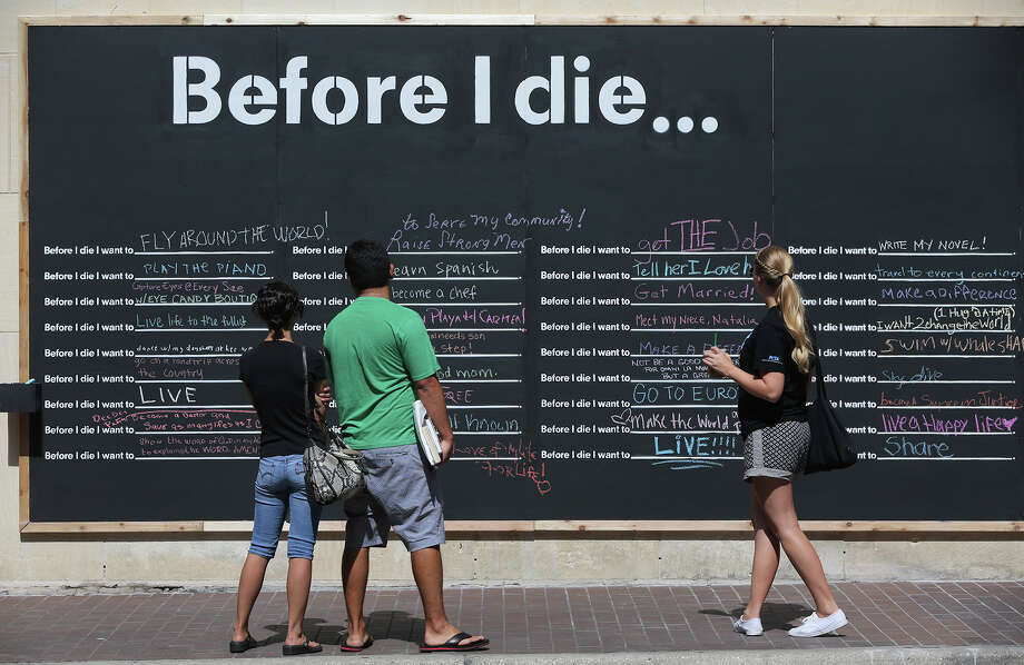 """Vanessa and Eloy Morin look at the """"Before I Die"""" wall at Navarro and Houston streets along with Kelsey Johnson (right). The interactive public art exhibit was started by artist Candy Chang in 2011 on an abandoned house in New Orleans. There are now hundreds of """"Before I Die"""" walls. Photo: John Davenport /San Antonio Express-News / ©San Antonio Express-News/John Davenport"""