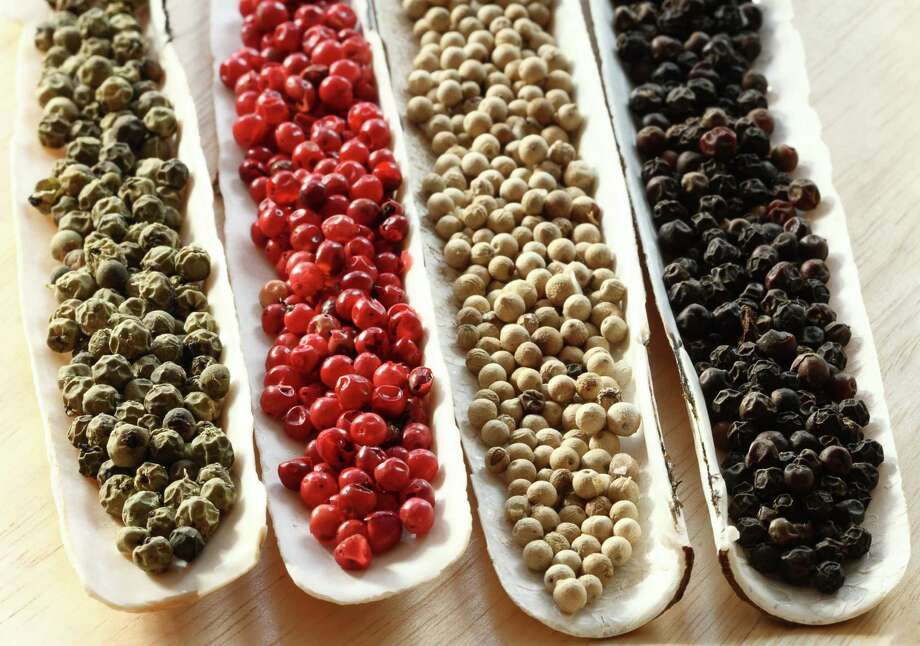 Peppercorns Spices in the sea shells on wood - Black peppercons, Green peppercons, Red peppercons, White  peppercons / handout / stock agency