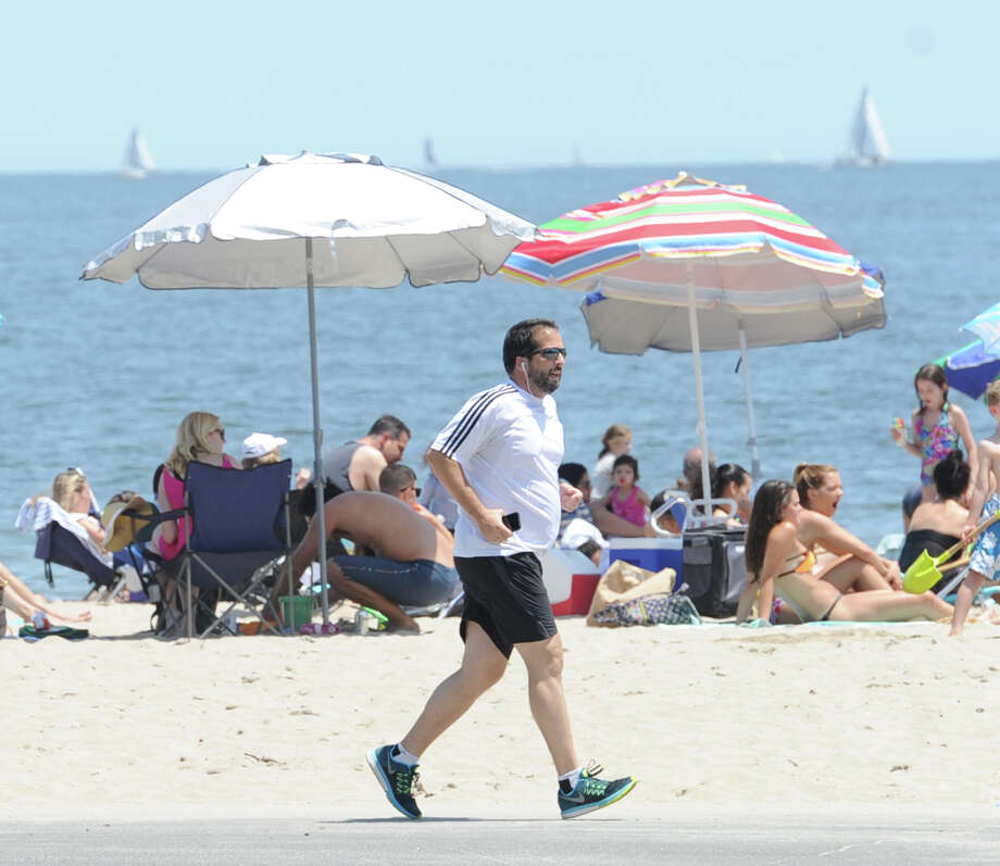 A jogger gets exercise near the beach at Greenwich Point. With the hottest days of summer just ahead, experts are reminding people to be careful in the sun and humidity. Photo: Bob Luckey Jr. / Hearst Connecticut Media / Greenwich Time