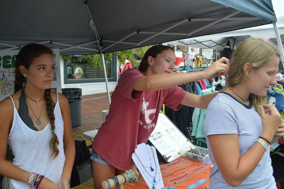 Erika Ehret, 15, of Stamford, gets a hand trying on a necklace from Shannon Eucci, 16, of New Canaan, who, along with Maddie Smith, 16, left, created Beads That Feed. The New Canaan High students have turned their hobby into a nonprofit project to support the New Canaan Food Bank. Photo: Jarret Liotta /For Hearst Connecticut Media