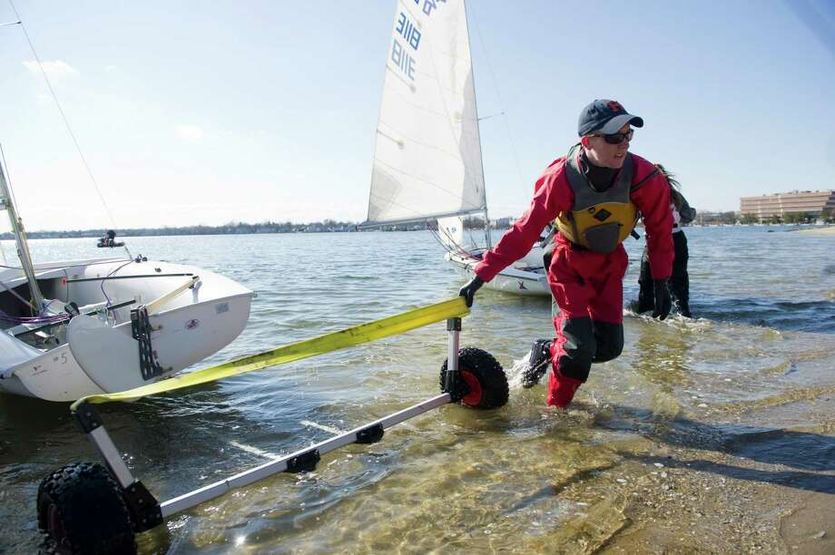 In this file photo, Elliott Morrill drags his boat back toward the shore during practice with the Stamford Schools Sail Team. Morrill was recently named to the Inter-Collegiate Sailing Association's All-Academic Team. Photo: Keelin Daly / ST / Stamford Advocate