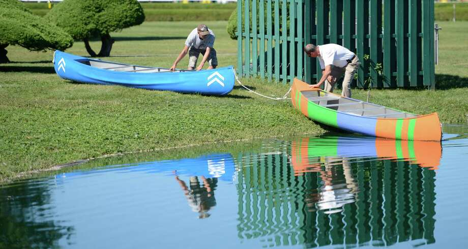 Two canoes painted in the colors of the dead heat winner's of the Travers Stakes were launched in to the infield lake of the Saratoga Race Course in Saratoga Springs, N.Y. Aug. 29, 2012.  The blue canoe represents the colors of Alpha who is owned Sheik Mohammed Al Maktoum of Dubai.  The multi-colored canoe is painted in the colors of Golden Ticket owned by Magic City Thoroughbred Investments. Photo: Skip Dickstein, TIMES UNION