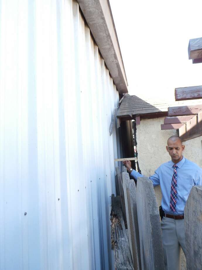 Oakland police said a man fleeing from officers after a traffic stop died after becoming wedged between two buildings on July 19, 2015. Here, Lt. Roland Holmgren measures the gap, which is less than a foot wide. Photo: Oakland Police Department