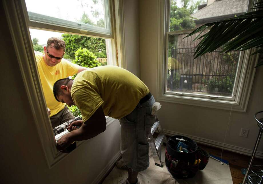 Rafael Calte, foreground, and Jeremy Devereaux with Houston Window Experts install a window at a house in Houston.