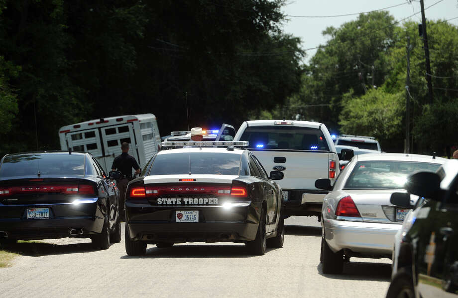 Law enforcement vehicles crowd County Line Road in Winnie on Monday. A 35-year-old white male was shot and killed by law enforcement officers in Winnie on Monday. Officers responded to a domestic disturbance call on County Line Road and found an individual who was in violation of a protection order. The individual resisted the officers, secured a weapon from his vehicle, and then exchanged gunfire with the officers. Trooper Richard Standifer said he believed the individual fired at least one shot, but that an investigation was still underway. Both DPS troopers and Chambers County Sheriff's deputies responded to the call and were involved in the incident.  Photo taken Monday 7/20/15  Jake Daniels/The Enterprise Photo: Jake Daniels / ©2015 The Beaumont Enterprise/Jake Daniels