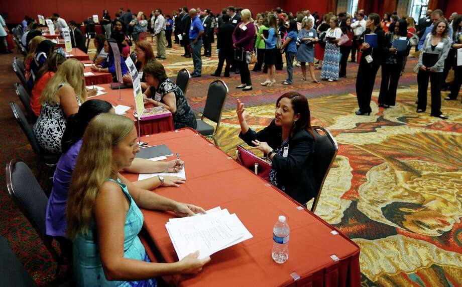 Educator Priscilla Lastrapes interviews with Stewart Elementary principal Traci Smith (left) and assistant principal Kristy Suarez at the San Antonio Independent School District job fair at the Henry B. Gonzalez Convention Center on Saturday, July 18, 2015. Several hundred prospective educators waited to meet with their potential SAISD employers. Teaching positions from elementary to high school were available. Smith was specifically looking to hire bilingual teachers at her school from kindergarten to fourth grade. (Kin Man Hui/San Antonio Express-News) Photo: Kin Man Hui, Staff / San Antonio Express-News / ©2015 San Antonio Express-News