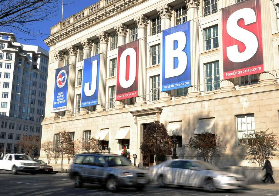 A jobs sign hangs above the entrance to the U.S. Chamber of Commerce building in Washington, D.C.  in this December 13, 2011 file photo. New claims for US unemployment benefits rose modestly last week but the overall trend showed fewer layoffs, government data released September 19, 2013 showed. Initial jobless claims totaled 309,000 in the week ending September 14, up by 15,000 from the prior week's revised 294,000 reading, the Labor Department said. The increase was less than analysts expected, with the average total claims estimate at 340,000.AFP PHOTO / Karen BLEIER / FILESKAREN BLEIER/AFP/Getty Images Photo: Karen Bleier, AFP/Getty Images