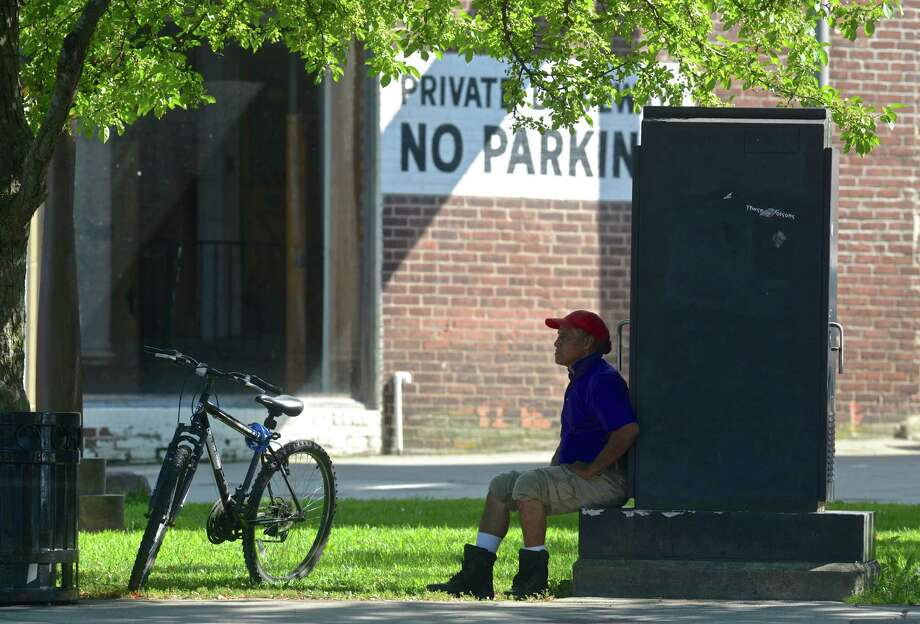 Luis Pomavilla, of Danbury, finds a shady spot to cool off on Monday afternoonat Main Street and Kennedy Avenue in Danbury. Photo: H John Voorhees III / Hearst Connecticut Media / The News-Times