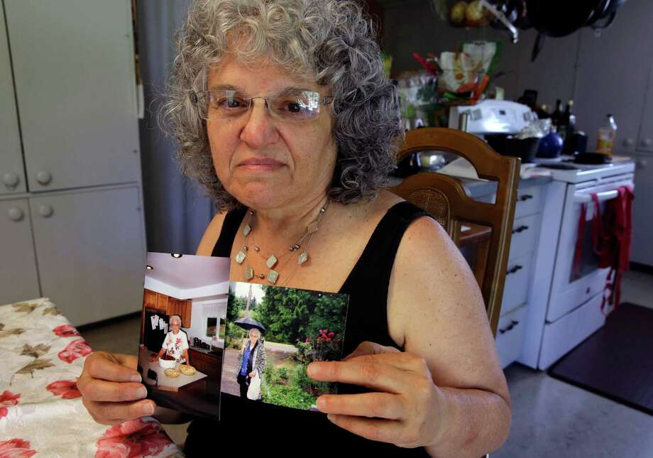 Roslyn Duffy holds two photos of her late mother, Evelyn Nappa, at her home in Seattle. Duffy had to scramble to find a home willing to take Medicaid payments after her mother was evicted from a Seattle assisted-living facility. Photo: Ted S. Warren /Associated Press / AP