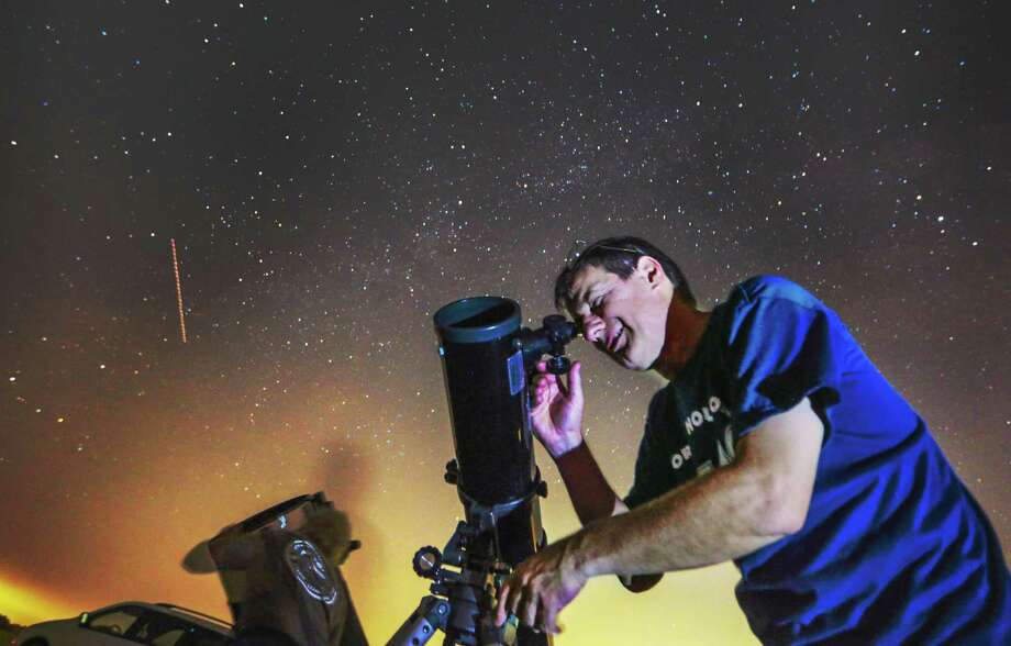 (l-r) Blair Traxler and James Billings look at the night skies with there telescopes Thursday July 17, 2015 in Montgomery, Texas. The two are members of the North Houston Astronomy Club. To escape the light pollution of the surrounding communities, the club uses a ranch in Montgomery as a dark site for there star gazing. (BILLY SMITH / Houston Chronicle) 