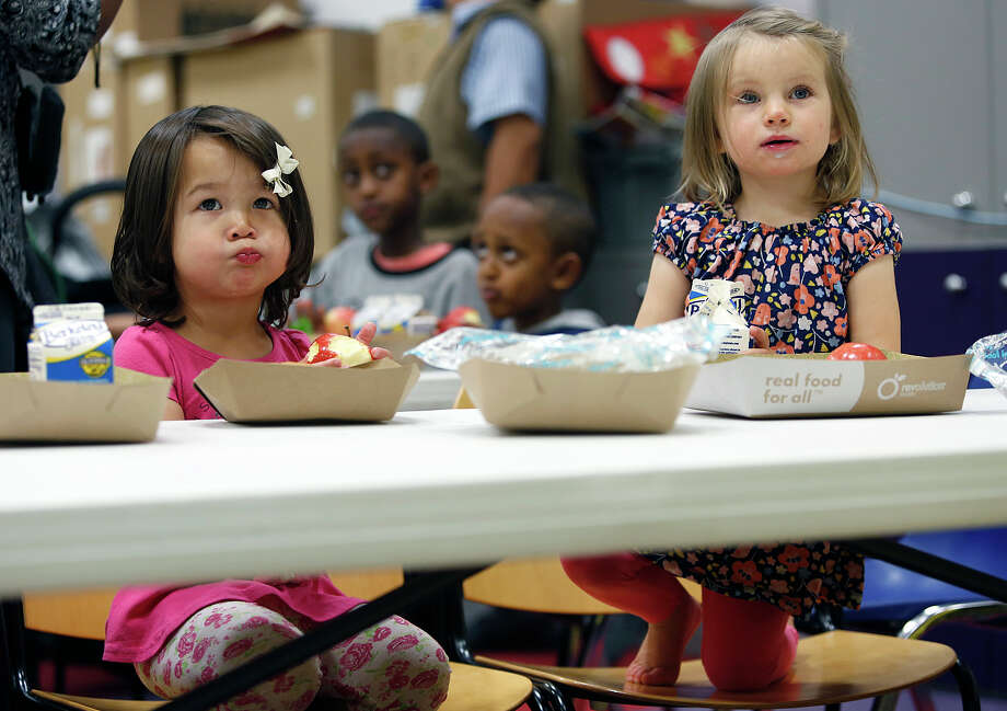 Addison, 2, (left) and Mia, 23 months, eat lunch at the children's center of the Main Library in San Francisco as part of a free summer meal program in the city. Photo: Liz Hafalia / Photos By Liz Hafalia / The Chronicle / ONLINE_YES