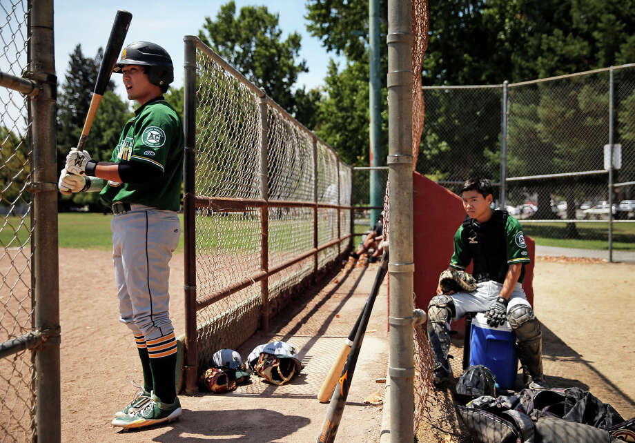 The Lodi Templars' Justin Uemura (left), prepares to bat as Scott Sasaki puts on his catcher's gear during the Japanese American Citizens League game against the San Francisco Hawks Sunday in San Bruno. Photo: Carlos Avila Gonzalez / Photos By Carlos Avila Gonzalez / The Chronicle / ONLINE_YES