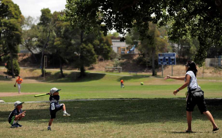 Shani Yamamoto (righ) pitches to her son Rylen, 4, as her son Reyn, 7, catches during the baseball game between the Lodi Templars and the S.F. Hawks. Photo: Carlos Avila Gonzalez / Photos By Carlos Avila Gonzalez / The Chronicle / ONLINE_YES