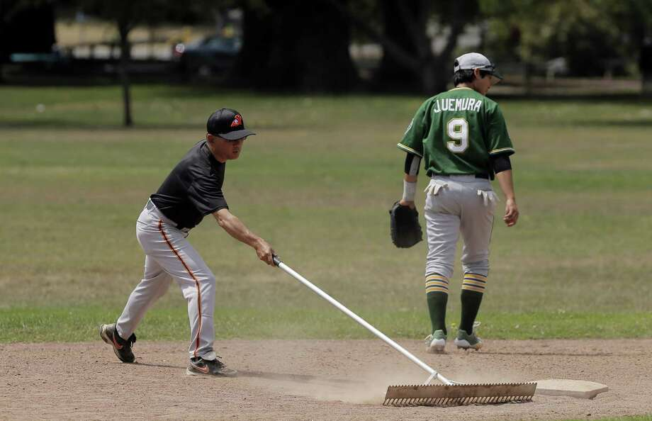 Derek Furuichi, manager for the San Francisco Hawks, preps the field near second base before the baseball game between the Lodi Templars and the San Francisco Hawks at Lara Field in San Bruno, Calif., on Sunday, July 19, 2015. The Templars and Hawks are part of a Japanese-American amateur baseball league, which is in danger of folding after 100 years because players are getting older, or some teams have shut down because of lack of player interest. Photo: Carlos Avila Gonzalez / The Chronicle / ONLINE_YES