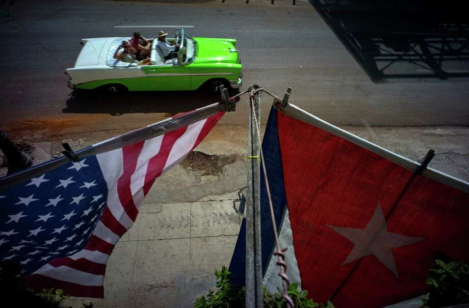 "U.S., and a Cuban national flags hang from a balcony in Old Havana on Monday to mark the restored full diplomatic relations between the two nations. The opening of the Cuban Embassy in  Washington, D.C., was commemorated in a morning ceremony. ""I would have walked from Miamia for this,"" said one observer. here will n force just after midnight Sunday and the diplomatic missions of each country were upgraded from interests sections to embassies. (AP Photo/Ramon Espinosa) Photo: Ramon Espinosa, STF / AP"