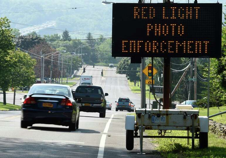 Vehicles travel past a sign notifying the motorist that the red-light cameras are working at the int