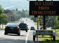 Vehicles travel past a sign notifying the motorist that the red-light cameras are working at the intersection of Shaker Road and Northern Boulevard Monday July 20, 2015 in Albany, N.Y.       (Skip Dickstein/Times Union)