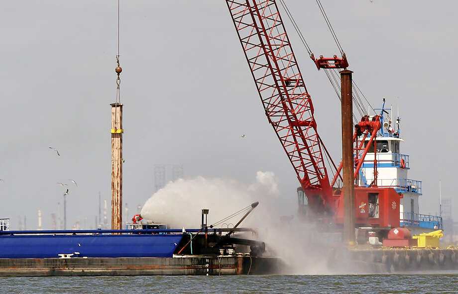 Authorities hose down a barge to keep it from re-igniting after it collided with another barge and burst into flames at about 1:20 a.m. Monday. Photo: Cody Duty, Staff / © 2015 Houston Chronicle