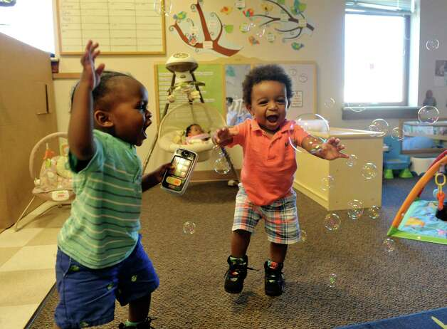 Cassidy, left, 15 months, and Quadir, 15 months, chase bubbles in the infant room  at the CEO Head Start program on Monday, July 20, 2015, in Troy, N.Y.  Better access to early childhood programs is seen as a way to improve child well-being. (Paul Buckowski / Times Union) Photo: PAUL BUCKOWSKI / 00032686A